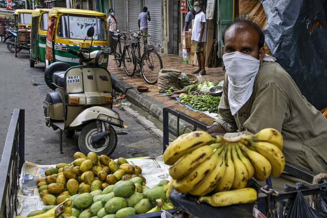 A street side fruit vendor has his face covered as a precaution against the coronavirus in Kolkata, India, Tuesday, July 21, 2020. With a surge in coronavirus cases in the past few weeks, state governments in India have been ordering focused lockdowns in high-risk areas to slow down the spread of infections. (Photo by Bikas Das/AP Photo)