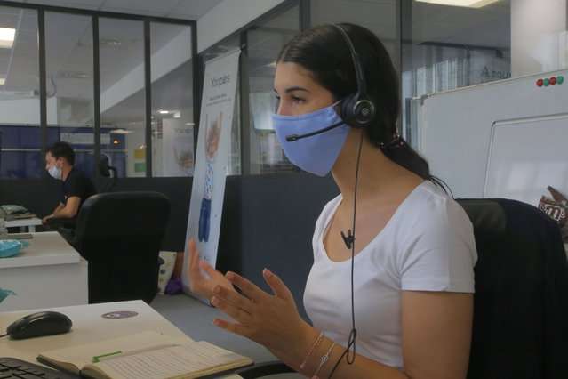 An employee wears a mask as she answers a call at a startup company, Wednesday August 19, 2020 in Paris. France is now mandating masks in all workplaces, from the Paris business district to factories in the provinces. The government is trying to contain growing virus infections but avoid shutting down the economy. The announcement makes France one of relatively few countries that's universally requiring workers to wear masks on the job, though they're routinely worn in many Asian countries. (Photo by Michel Euler/AP Photo)