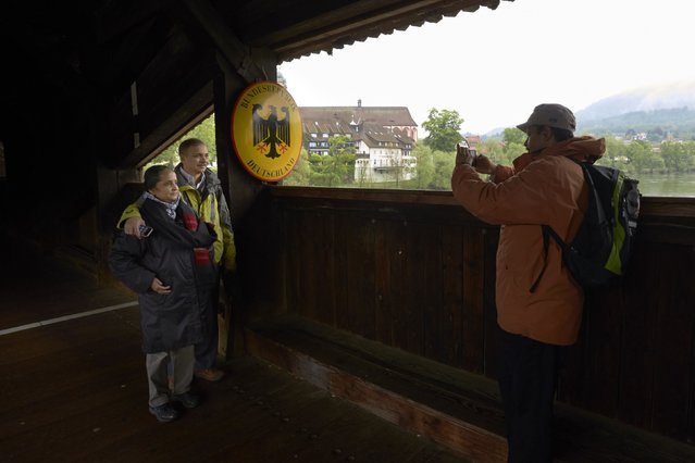 Tourists take a picture on a 400-year-old wooden bridge on the border between Switzerland (front) and Germany in Stein May 1, 2014. (Photo by Denis Balibouse/Reuters)