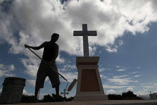 A man paints the tomb of a loved one the day before the annual Day of the Dead celebrations at the cemetery in Managua November 1, 2014. Thousands of Nicaraguans will visit cemeteries to honor their dead on November 2. (Photo by Oswaldo Rivas/Reuters)