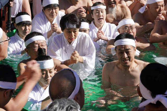 Japanese bathers pray for the healthy new year while dipping in a cold water tub with blocks of ice at a Teppozu Inari Shinto Shrine during a winter ritual in Tokyo, Sunday, January 14, 2018. (Photo by Shizuo Kambayashi/AP Photo)