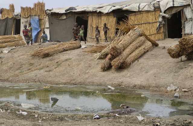 In this photo taken Sunday, December 9, 2018, children stand outside their straw huts across from a stagnant pond in the United Nations protection of civilians site in Bentiu, South Sudan. Six months ago planning ahead in civil war-torn South Sudan seemed impossible but now, after warring sides signed a new peace deal in September that the government vows will hold, some are starting to rebuild their lives. (Photo by Sam Mednick/AP Photo)