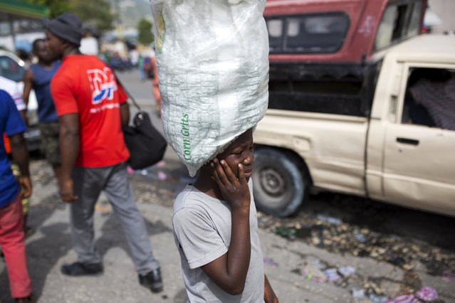 """In this May 23, 2017 photo, unpaid child servant Watson Saint Fleur balances a sack of water bags for sale, on his head in the streets of Petion-Ville, a suburb of Port-au-Prince, Haiti. He's one of Haiti's """"restaveks"""", a term to describe children whose poor parents hand them over to others in hopes they'll have opportunities to escape a dead-end life or at least get more food. (Photo by Dieu Nalio Chery/AP Photo)"""