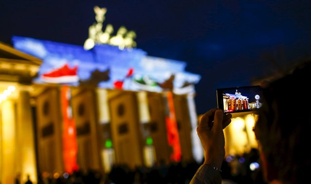 "A man takes a picture of a light installation at the Brandenburg Gate during the opening day of the ""Festival of Light"" show in Berlin, Germany, October 9, 2015. (Photo by Hannibal Hanschke/Reuters)"