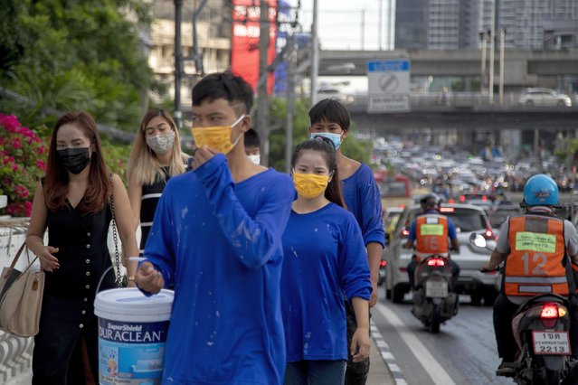 Office workers and construction workers with face masks walk in a side walk in Bangkok, Thailand, Thursday, September 3, 2020. Thailand's prime minister on Wednesday congratulated his countrymen on the nation having achieved 100 days without a new confirmed locally transmitted case of the coronavirus, even as security along the border with Myanmar is being stepped up as a measure against the disease. (Photo by Gemunu Amarasinghe/AP Photo)
