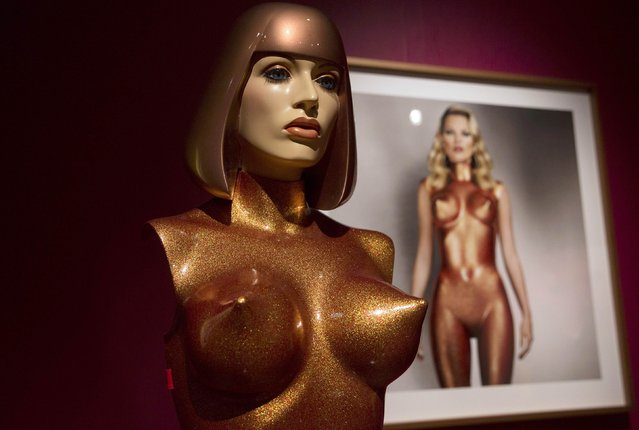 """A costume worn by model Kate Moss for the 2013 photograph """"Body Armour"""" is displayed next to a copy of the image at a press viewing of the artist's exhibition """"Allen Jones RA"""" at the Royal Academy of Arts in London November 11, 2014. (Photo by Neil Hall/Reuters)"""