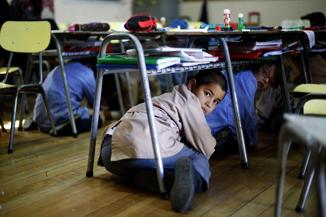Students take cover under their desk inside a school during an earthquake drill in Santiago, November 13, 2014. (Photo by Ivan Alvarado/Reuters)