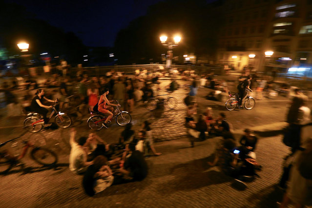 People sit at Admiralsbruecke bridge at night time in Berlin, Germany, August 27, 2016. Many people spend time on this bridge during the summer, enjoying the sunset and warm nights, drinking beer and listening to street musicians. (Photo by Hannibal Hanschke/Reuters)