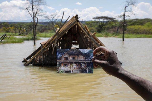 Camp manager James Owuor, holds a photo showing a structure before it was submerged under rising water due to months of unusually heavy rains, in lake Baringo, Kenya, August 25, 2020. (Photo by Baz Ratner/Reuters)