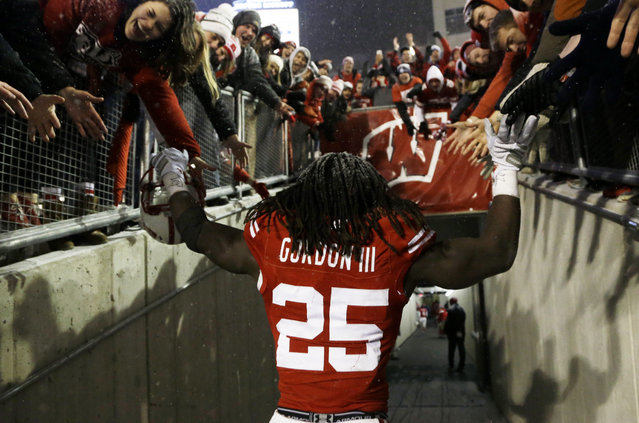 Wisconsin's Melvin Gordon celebrates with fans after their 59-24 win over Nebraska in an NCAA college football game Saturday, November 15, 2014, in Madison, Wis. Gordon rushed for a major college-record 408 yards and four touchdowns in the game. (Photo by Morry Gash/AP Photo)