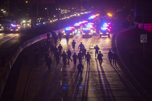 California Highway Patrol officers walk to clear the 101 freeway from protesters in Los Angeles, California, following Monday's grand jury decision in the shooting of Michael Brown in Ferguson, Missouri, November 25, 2014. (Photo by Mario Anzuoni/Reuters)