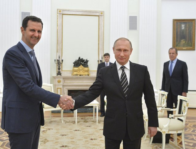 Russian President Vladimir Putin (R) shakes hands with Syrian President Bashar al-Assad during a meeting at the Kremlin in Moscow, Russia, October 20, 2015. Assad made a surprise visit to Moscow on Tuesday evening to thank Putin for launching air strikes against Islamist militants in Syria. (Photo by Alexei Druzhinin/Reuters/RIA Novosti/Kremlin)