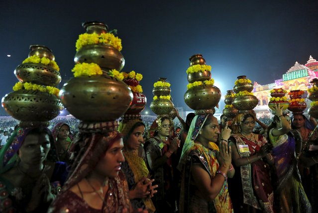 Hindu women carrying decorated metal pitchers pray after taking part in Garba, a traditional folk dance, during the celebrations to mark the Navratri festival at Surat in the western state of Gujarat, India, October 21, 2015. (Photo by Amit Dave/Reuters)