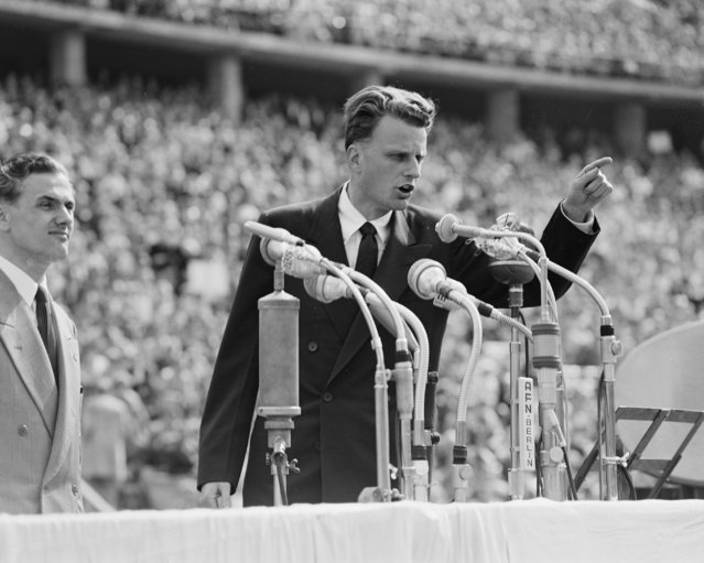 In this June 27, 1954 file photo, Evangelist Billy Graham speaks to over 100,000 Berliners at the Olympic Stadium in Berlin, Germany.   Graham, who transformed American religious life through his preaching and activism, becoming a counselor to presidents and the most widely heard Christian evangelist in history, has died. Spokesman Mark DeMoss says Graham, who long suffered from cancer, pneumonia and other ailments, died at his home in North Carolina on Wednesday, Feb. 21, 2018. He was 99. (Photo by AP Photo)