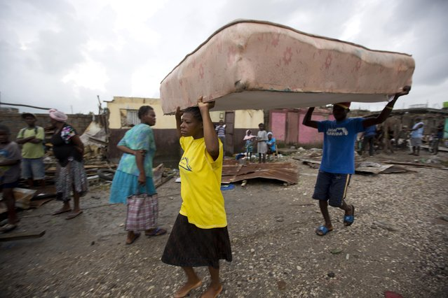 Residents carry a mattress to a shelter after homes were destroyed by Hurricane Matthew in Les Cayes, Haiti, Thursday, October 6, 2016. (Photo by Dieu Nalio Chery/AP Photo)