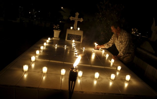 A man places candles on the grave during a vigil at a cemetery in Barva de Heredia, Costa Rica, October 31, 2015. (Photo by Juan Carlos Ulate/Reuters)