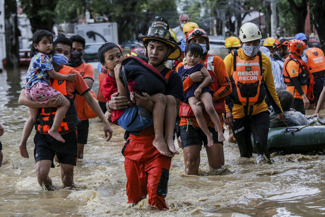 Rescuers carry children out from a flooded street due to heavy rains brought by Typhoon Vamco in Providence village in Marikina City, east of Manila, Philippines, Thursday. November 12, 2020. (Photo by Basilio Sepe/AP Photo)