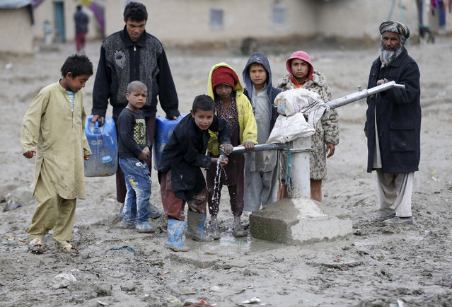 Children drink water from a public water pump on the outskirts of Kabul, Afghanistan, March 4, 2016. (Photo by Omar Sobhani/Reuters)
