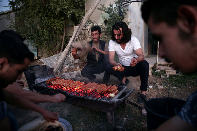 Crew of a film directed by Humam Husari grill meat after the end of filming in the rebel held Douma neighbourhood of Damascus, Syria October 6, 2016. (Photo by Bassam Khabieh/Reuters)
