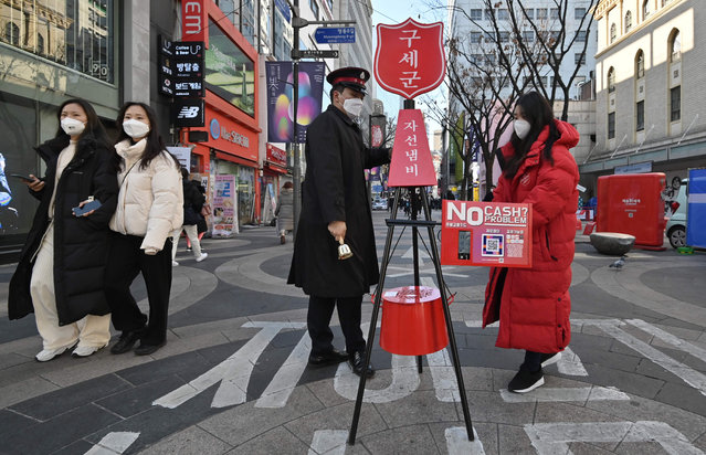 A Salvation Army officer sets up a charity pot for a year-end fundraising campaign at the Myeongdong shopping district in Seoul on December 1, 2020, as the Salvation Army launched its year-end charity campaign for poor people. (Photo by Jung Yeon-je/AFP Photo)