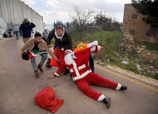 A Palestinian protester wearing a Santa Claus costume is carried by medics after inhaling tear gas fired by Israeli troops during clashes at Bethlehem checkpoint in the West Bank city of Bethlehem, Tuesday, December 23, 2014. (Photo by Majdi Mohammed/AP Photo)