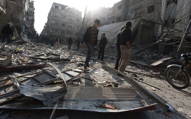 Men inspect a site hit by what activists said was an air strike by forces loyal to Syria's President Bashar al-Assad in the Duma neighbourhood of Damascus December 27, 2014. (Photo by Badra Mamet/Reuters)