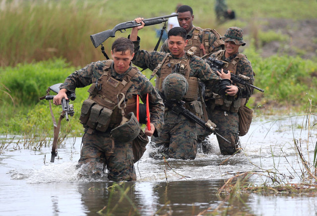 U.S. military forces cross a flooded area near the shore during the annual Philippines-US amphibious landing exercise (PHIBLEX) at San Antonio, Zambales province, Philippines October 7, 2016. (Photo by Romeo Ranoco/Reuters)