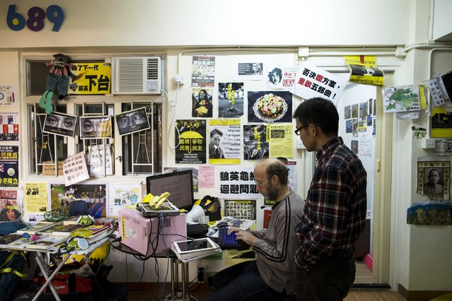 British freelance writer Stephen Thompson (L) and Chinese traveller David King react at a guesthouse with a pro-democracy theme in Hong Kong December 30, 2014. (Photo by Tyrone Siu/Reuters)