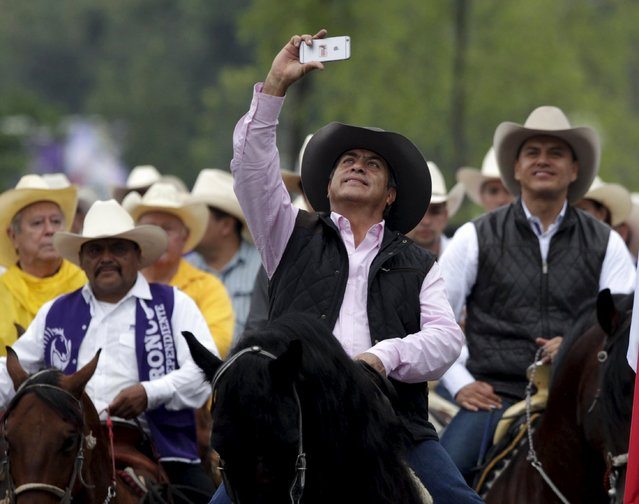 Jaime Rodriguez (C) takes a selfie as he rides on his horse accompanied by supporters at Fundidora park, after taking the oath on Saturday as the new governor of the Nuevo Leon state in Monterrey, Mexico October 4, 2015. (Photo by Daniel Becerril/Reuters)