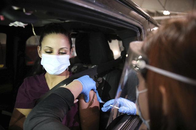 Rachel Shields-Carnley, a nurse at Ascension St. John, receives the Pfizer-BioNTech COVID-19 vaccine, December 15, 2020 in Tulsa , Okla. (Photo by Mike Simons/Tulsa World via AP Photo)