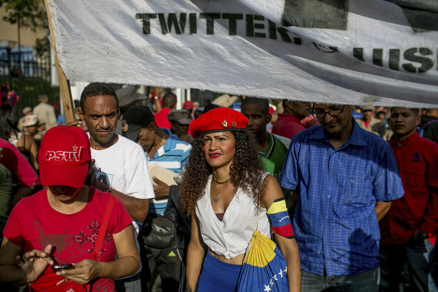 """Government supporters listen to a speech by Venezuela's president Nicolas Maduro during a political rally against Congress in Caracas, Venezuela, Tuesday, October 25, 2016. After the government suspended a recall referendum seeking President Nicolas Maduro's removal last week, the opposition-controlled congress began debating his """"constitutional situation"""". Lawmakers vow to present evidence that Maduro is a dual Colombian citizen and therefore constitutionally ineligible to hold Venezuela's highest office. (Photo by Alejandro Cegarra/AP Photo)"""