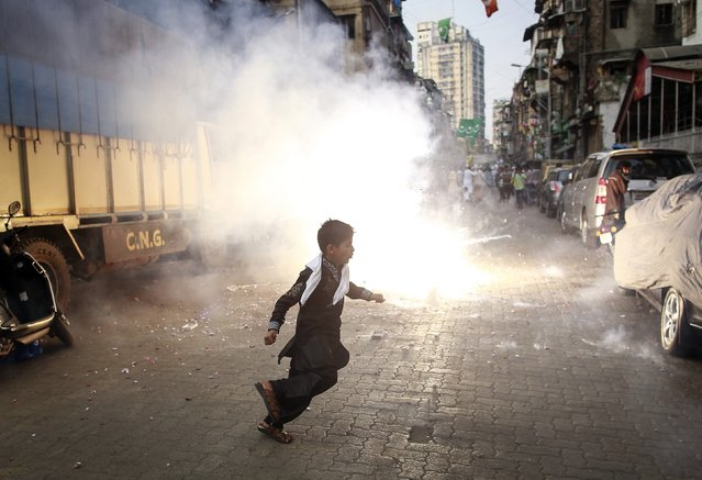 A boy runs as fireworks explode during a procession to mark Eid-e-Milad-ul-Nabi, the birthday celebration of Prophet Mohammad, in Mumbai January 4, 2015. (Photo by Danish Siddiqui/Reuters)