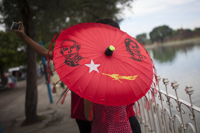 A group of people with an umbrella displaying pictures of Myanmar's opposition leader Aung San Suu Kyi, her late father General Aung San, and the logo of Suu Kyi's National League for Democracy party take pictures of themselves in Mandalay, the second largest city of Myanmar, Friday, September 18, 2015. (Photo by Hkun Lat/AP Photo)
