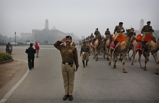 An Indian Border Security Force (BSF) soldier salutes to the marching ground as his camel mounted contingent practices a march during rehearsals for the Republic Day parade amidst the morning fog, in New Delhi, India, Wednesday, January 7, 2015. (Photo by Manish Swarup/AP Photo)