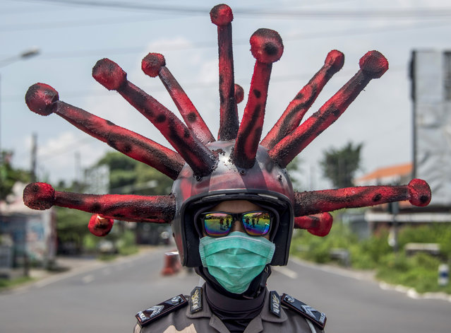 An Indonesian police officer wearing a Covid-19 coronavirus themed helmet conducts a campaign and disinfects motorists' vehicles in Mojokerto, East Java on April 3, 2020. (Photo by Juni Kriswanto/AFP Photo)