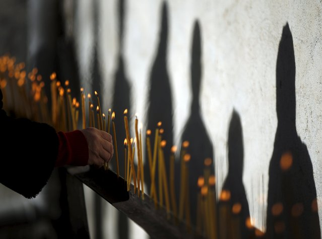 People cast shadows on the wall as they light candles during St. George's Day celebration in the village of Ikalto, Georgia, November 23, 2015. (Photo by David Mdzinarishvili/Reuters)