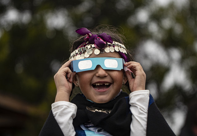 Magdalena Nahuelpan, a Mapuche Indigenous girl, looks at a total solar eclipse using special glasses in Carahue, La Araucania, Chile, Monday, December 14, 2020. The total eclipse was visible from Chile and the northern Patagonia region of Argentina, and as a partial solar eclipse in Bolivia, Brazil, Ecuador, Paraguay, Peru and Uruguay. (Photo by Esteban Felix/AP Photo)