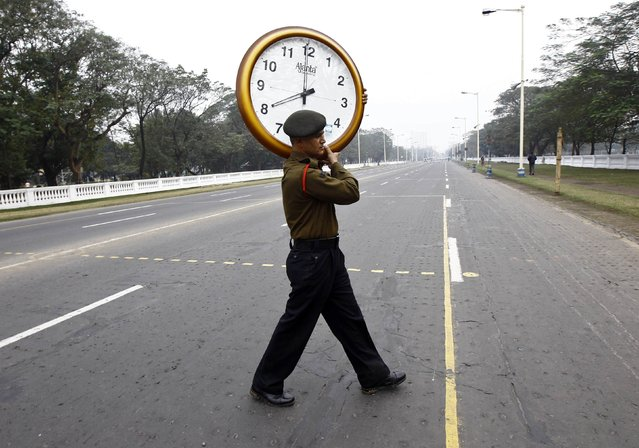 An Indian army soldier crosses a road with a wall clock which was temporary fixed at the side of a road to monitor parade timing, after the rehearsal for the Republic Day parade in Kolkata January 4, 2015. India will celebrate its annual Republic Day on January 26. (Photo by Rupak De Chowdhuri/Reuters)