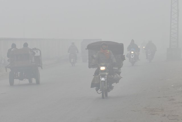Commuters make their way amid dense fog on a cold winter morning in Lahore on December 26, 2020. Various cities in eastern and central Pakistan continue to experience heavy fog, disrupting air and road transportation. Fog has its own criteria under which it develops, the visibility must reduce to less than 1 kilometre, the humidity levels must be more than 90 per cent, the air must be still and the sky clear. (Photo by Rana Sajid Hussain/Pacific Press/Rex Features/Shutterstock)