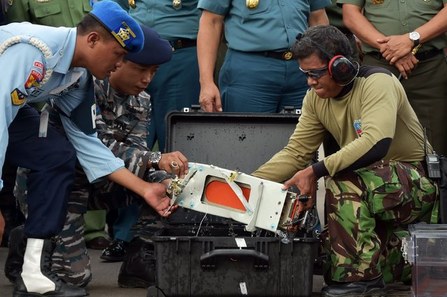 The flight data recorder of AirAsia QZ8501 is lifted out of a carrying case at the airbase in Pangkalan Bun, Central Kalimantan January 12, 2015. (Photo by Adek Berry/Reuters)