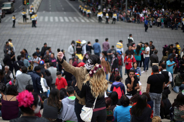 """A couple with their faces painted to look like the popular Mexican figure called """"Catrina"""" take a selfie in a procession to celebrate the upcoming annual Day of the Dead on November 1 and 2, at Angel de la Independencia monument, in Mexico City, Mexico, October 23, 2016. (Photo by Edgard Garrido/Reuters)"""