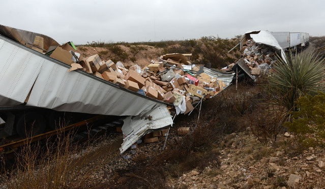Boxes are strewn out of a UPS train car that was damaged when a Texas Department of Criminal Justice transport bus lost control on Interstate 20, went down an embankment and crashed into the moving train Wednesday morning, January 14, 2014 near Penwell, Texas. (Photo by Mark Sterkel/AP Photo/Odessa American)