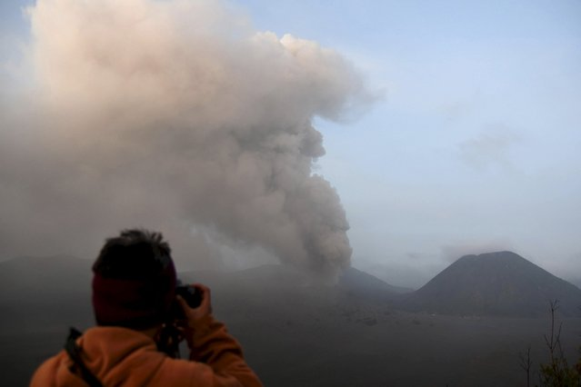 A visitor takes a picture of volcanic ash spewing from Mount Bromo, in East Java, Indonesia December 6, 2015 in this photo taken by Antara Foto. The Centre for Volcanology and Geological Hazard Mitigation has raised the warning level at Mount Bromo due to increased seismic activity. (Photo by M. Risyal Hidayat/Reuters/Antara Foto)