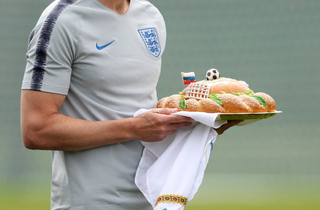 The England manager, Gareth Southgate, carries a welcome gift before a pre-World Cup training session at the Spartak stadium in Zelenogorsk near Saint Petersburg, Russia on June 13, 2018. (Photo by Lee Smith/Reuters)
