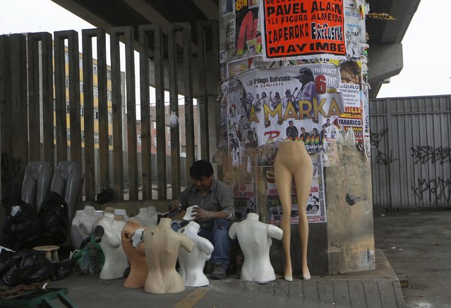 A man sells mannequins under the railway track of the Metro train in downtown Lima, Peru December 1, 2015. (Photo by Mariana Bazo/Reuters)