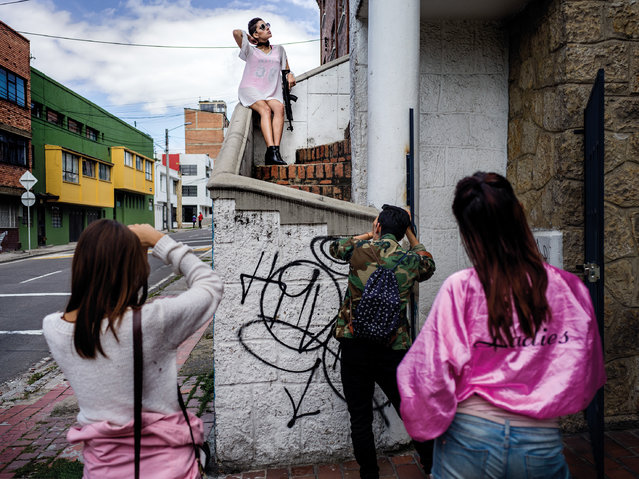 """A fashion shoot for a local brand """"Hunters Project Agency"""" in one of the wealthier neighbourhood in the North of Bogota. The model Astrid Sánchez Pinada is holding a plastic AK47 in her hand. """"Fashion reflects what's happening in the world, our country and in our streets"""", the fashion photographer explains. (Photo by Mads Nissen/Politiken/The Guardian/Panos Pictures)"""