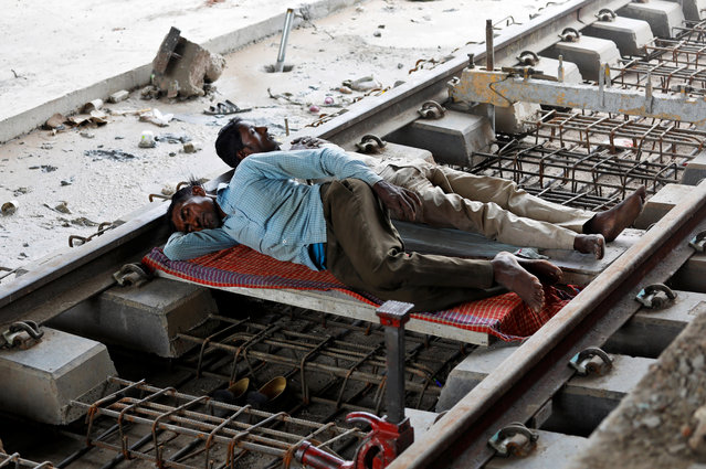 Workers sleep on a railway track under repair in New Delhi, India, June 15, 2018. (Photo by Saumya Khandelwal/Reuters)