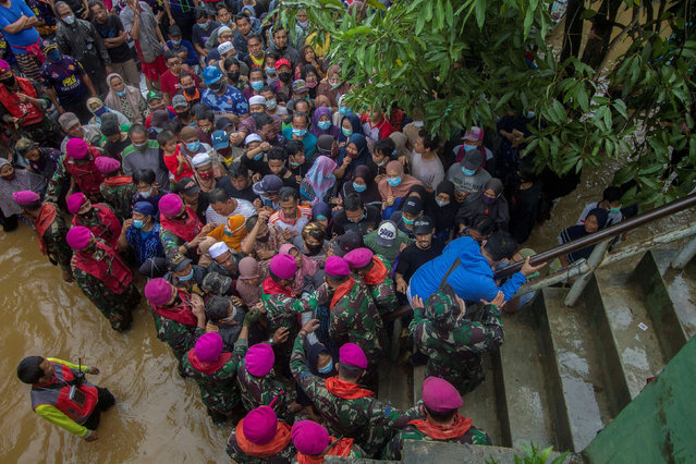 Residents affected by floods gather for aid assistance during a visit by the Indonesian president, Joko Widodo, in South Kalimantan province, Indonesia on January 17, 2021/ (Photo by Antara Foto via Reuters)