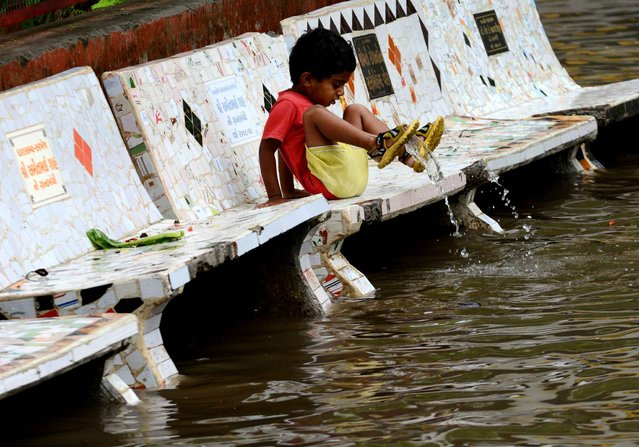 A child at the Shrinand Nagar Residency reacts to floodwaters in Ahmedabad, India, on July 5, 2013. Heavy rains lashed many parts of Gujarat state with the Indian Meteorological Department predicting heavy rains for the next 24 hours. (Photo by Sam Panthaky/Getty Images)