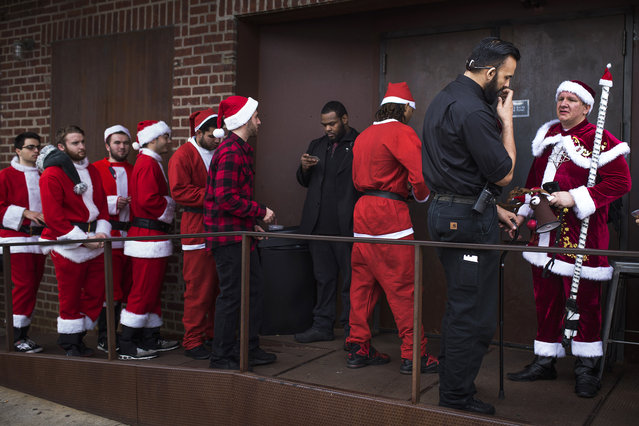Security check ids of Revelers dressed in holiday theme costumes as they enter a club during SantaCon in New York Saturday, December 12, 2015, in New York. Tracing its origins to a prankish, anti-consumerist gathering in San Francisco in 1994, SantaCon has mushroomed into events in hundreds of cities. (Photo by Andres Kudacki/AP Photo)